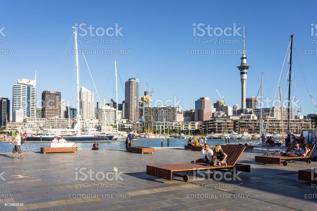 People relax on large wooden public long chairs in the Wynyard Quarter, Auckland stock photo