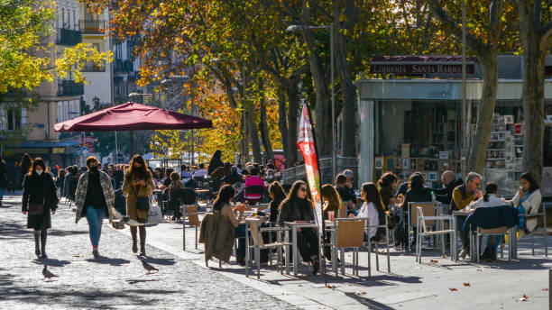 People relax on the terrace cafe in the popular Malasana neighborhood in central Madrid, Spain stock photo