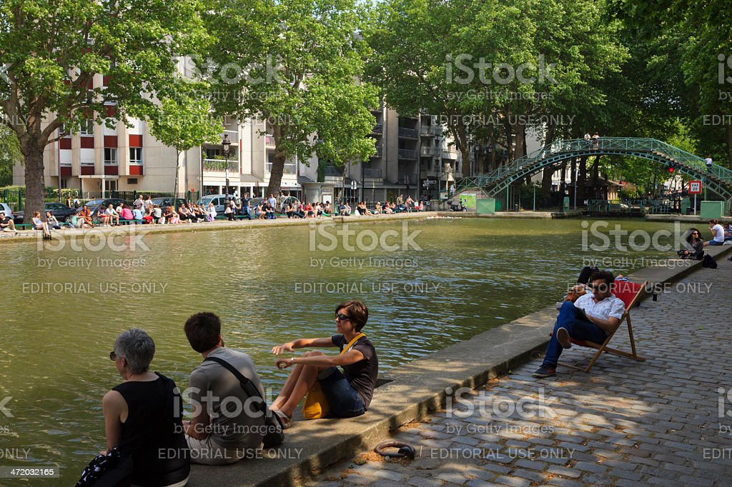 people relaxing along the Marais river in Paris stock photo