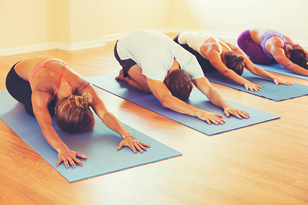 People Relaxing and Doing Yoga Yoga Class, Group of People Relaxing and Doing Yoga. Childs Pose. Wellness and Healthy Lifestyle. yoga class stock pictures, royalty-free photos & images