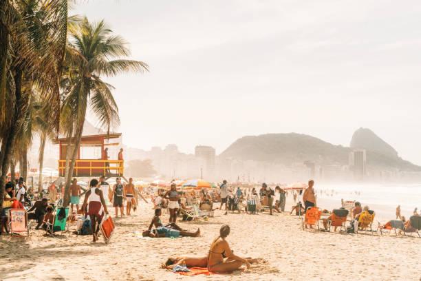 menschen entspannen und sonnenbaden am berühmten strand copacabana, rio de janeiro, brasilien - rio de janeiro stock-fotos und bilder