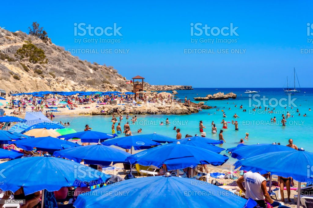 People relaxing and sunbathing at Konnos beach stock photo