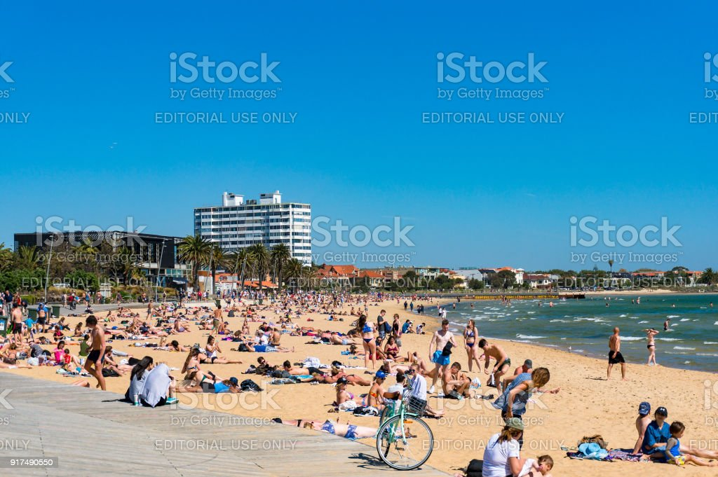 People relaxing and sunbathing in St.Kilda beach on sunny day stock photo