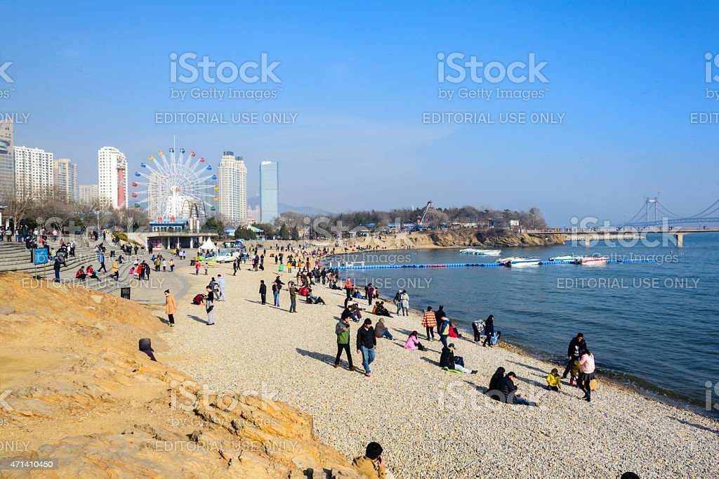 people relaxing at the beach at Xinghai park. stock photo