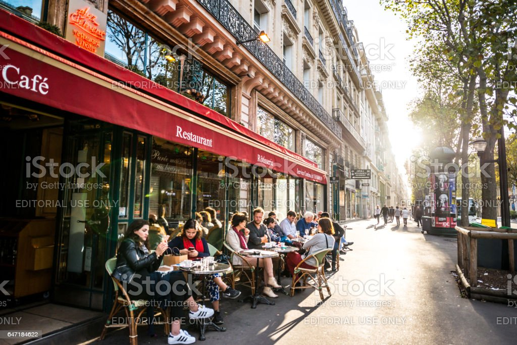 People relaxing, eating and drinking in restaurant in Paris, France stock photo