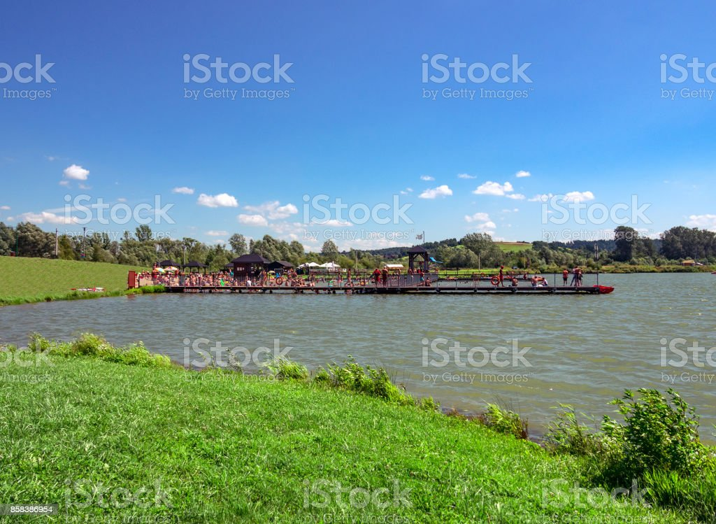 People relaxing in open pool on lake. Stary Sacz, Poland. stock photo