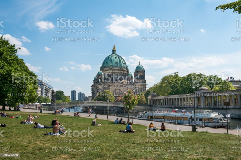 People relaxing on meadow in park  in Berlin with the Berlin Cathedral in background stock photo
