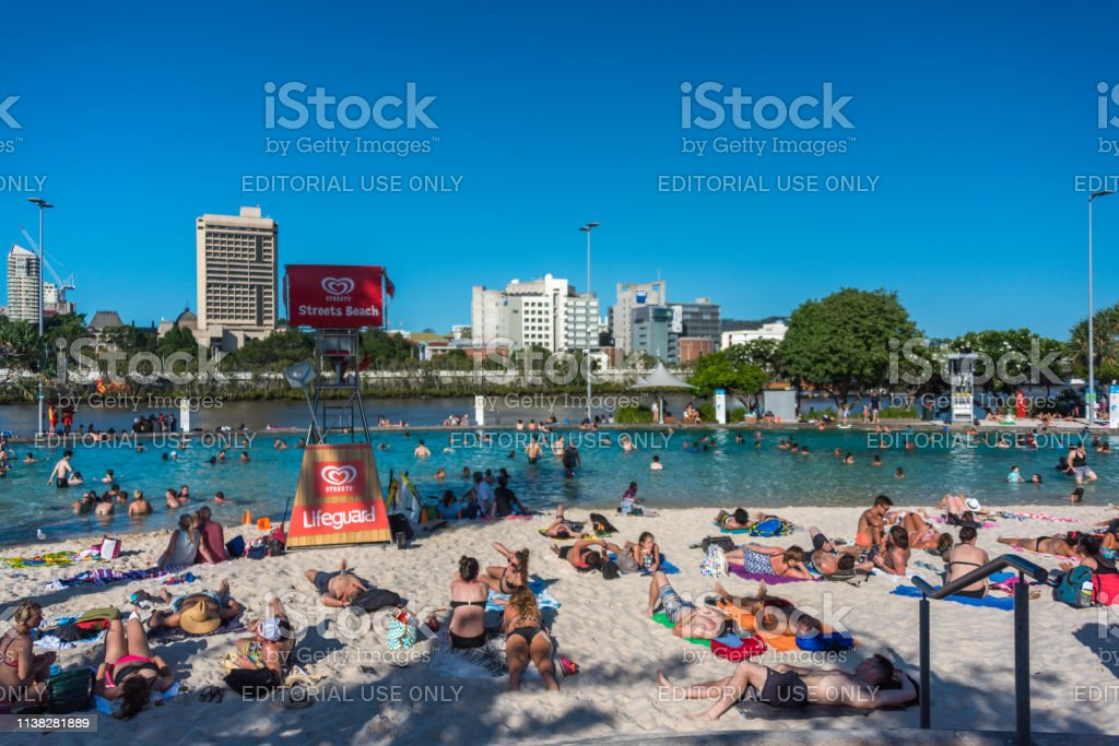 People relaxing on South Bank Parklands city beach on sunny day stock photo