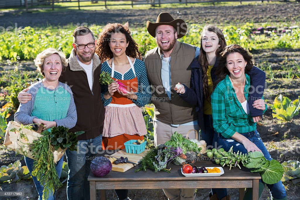A group of six people preparing fresh, organic vegetables on a table...