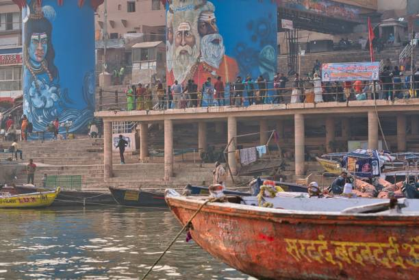 People resting and walking near a ghat in Varanasi, India Varanasi, India - December 21, 2019: Some people resting and some people walking on the stairs, near a ghat, on a sunny beautiful day in the holy city of Varanasi, India, where some clothes are also put on the ground to be dried in the sun, near some huge beautifully painted walls. dashashwamedh ghat stock pictures, royalty-free photos & images