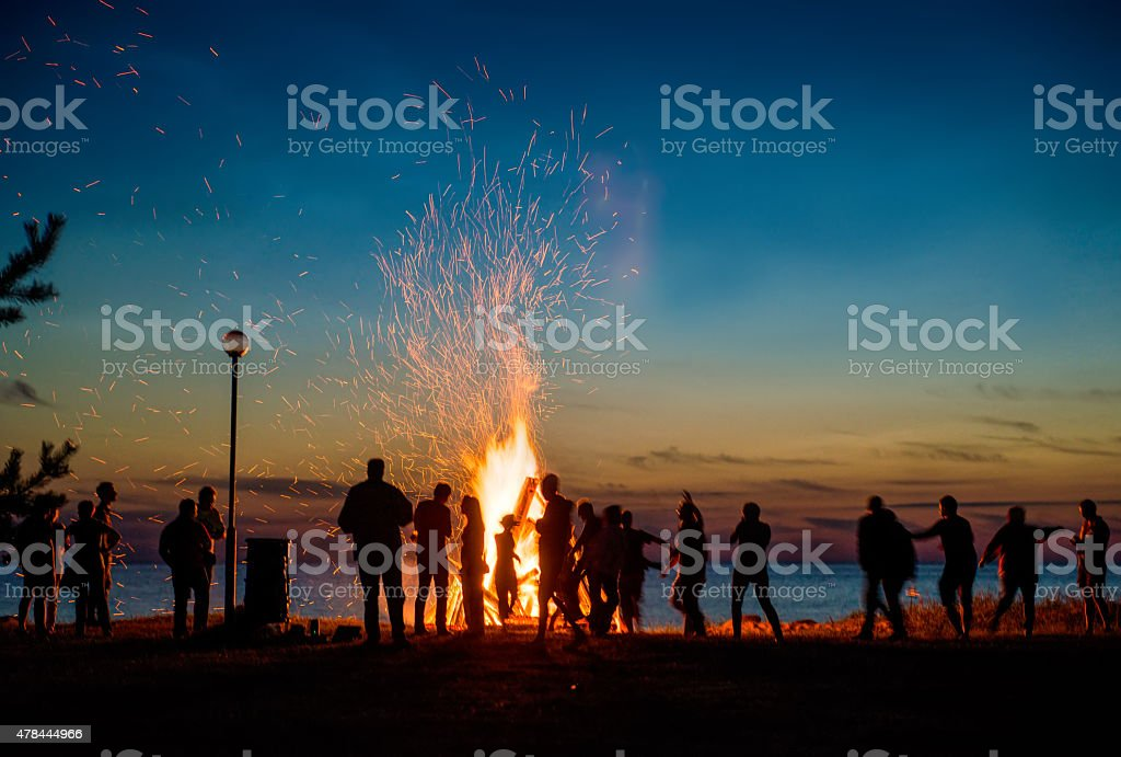 People resting near big bonfire outdoor stock photo