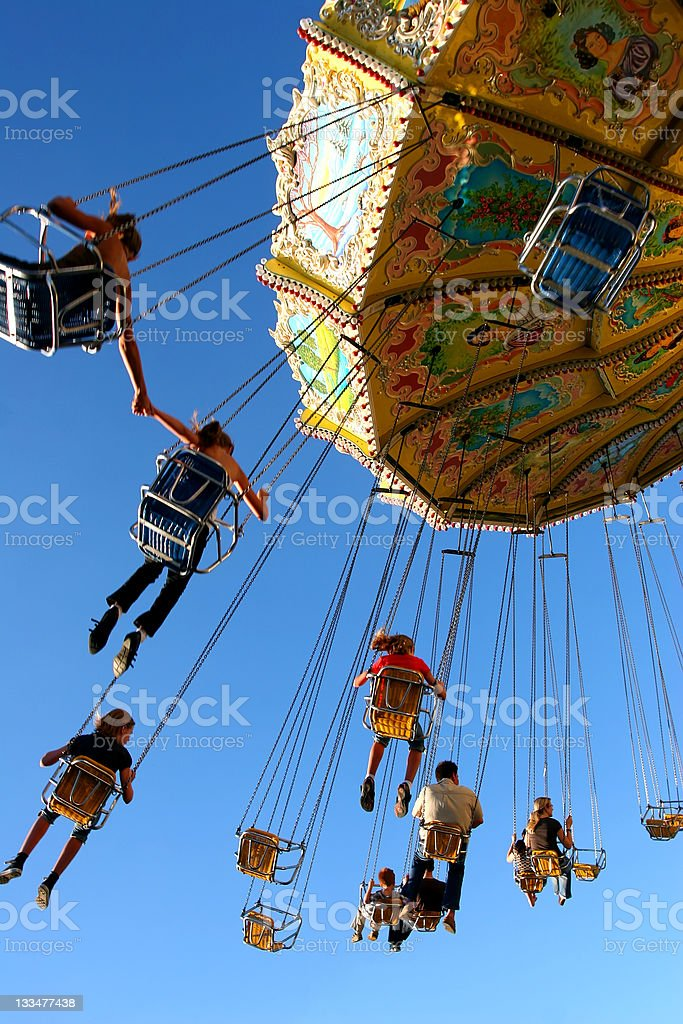 People ride a chairoplane in an amusement park stock photo
