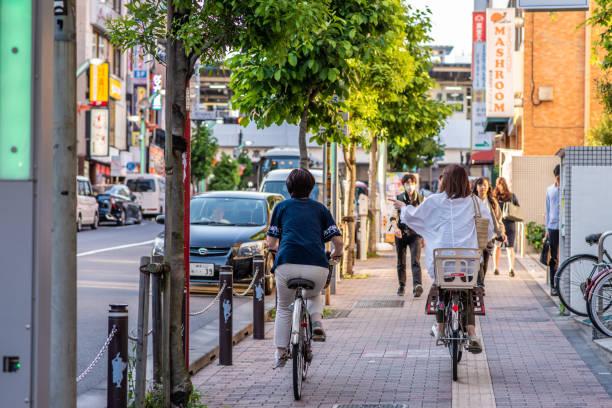 People ride bicycles on the sidewalk in the Koenji neighborhood, Tokyo,Japan stock photo