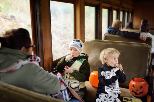 die menschen fahren im traditionellen zug express auf feiern halloween in der nähe von new york. - festzugskleidung stock-fotos und bilder