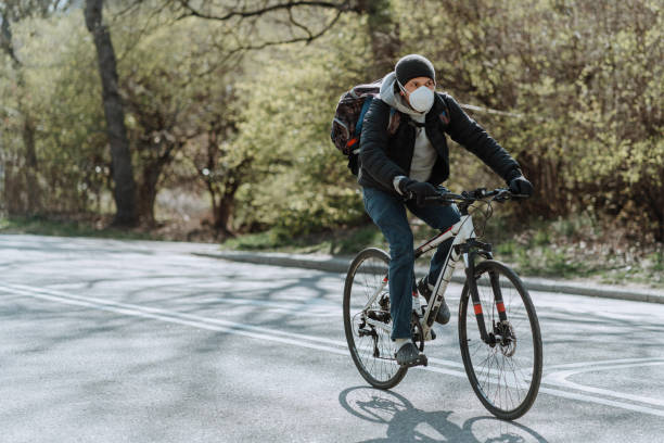 People riding a bicycle in Central Park wearing masks. stock photo