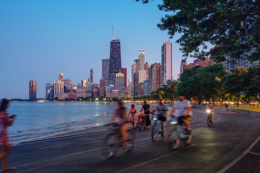 People riding bicycles at night with Chicago skyline in background