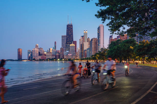 People riding bicycles at night with Chicago skyline in background stock photo