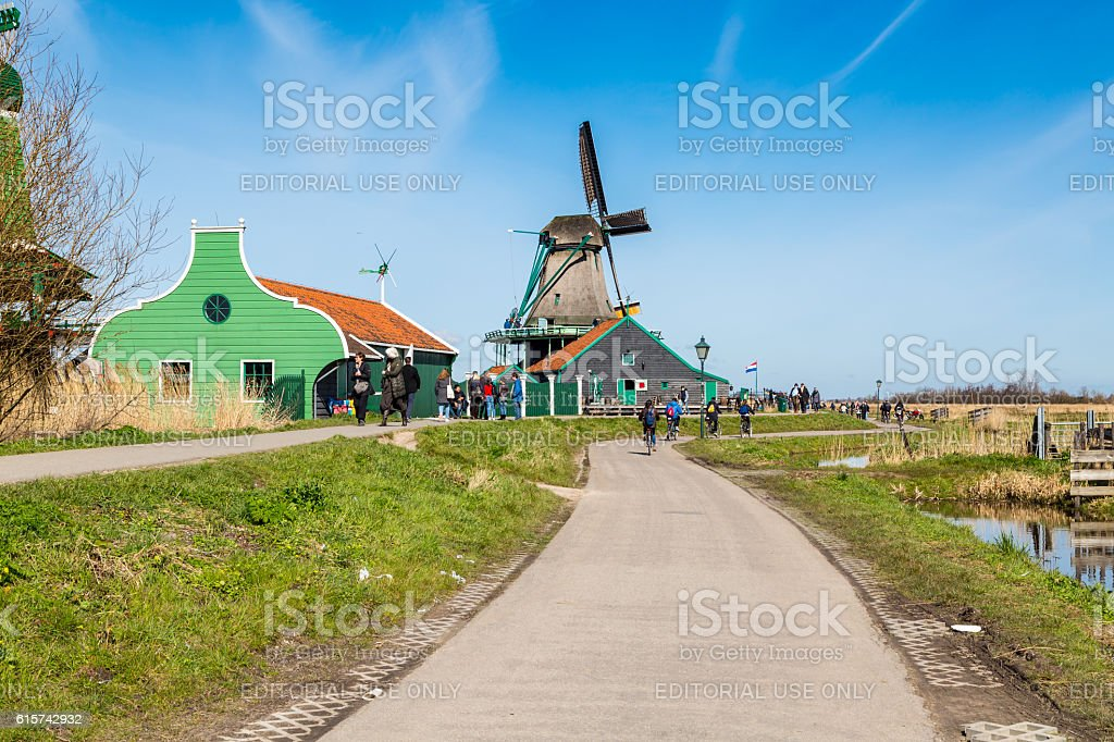 People riding bicycles, houses and windmill in Zaanse Schans, Holland stock photo