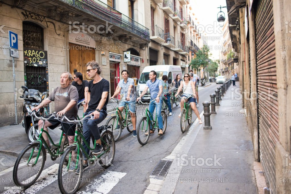 People riding bicycles in Gothic Quarter in Barcelona stock photo