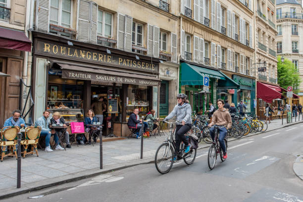 People riding bicycles in Marais in Paris stock photo