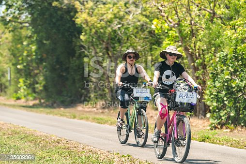 istock People riding bikes bicycles on trail sidewalk in park by beach and road in Captiva Fort Myers, Florida 1135609364
