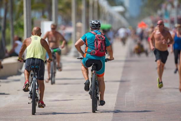 people riding bikes on hollywood beach fl memorial day weekend - memorial day weekend стоковые фото и изображения
