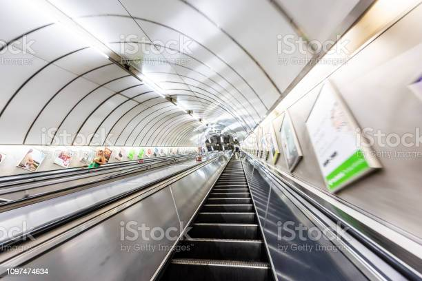 London, UK - June 26, 2018: People riding escalator up and down standing in Underground tube metro in Pimlico Victoria area of city through tunnel