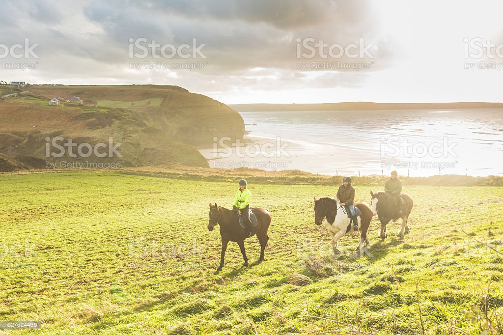 People riding horses in the countryside stock photo