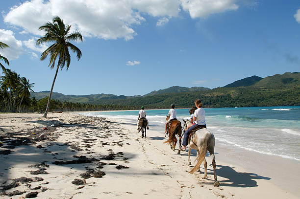 People riding horses on the beach of Rincon stock photo