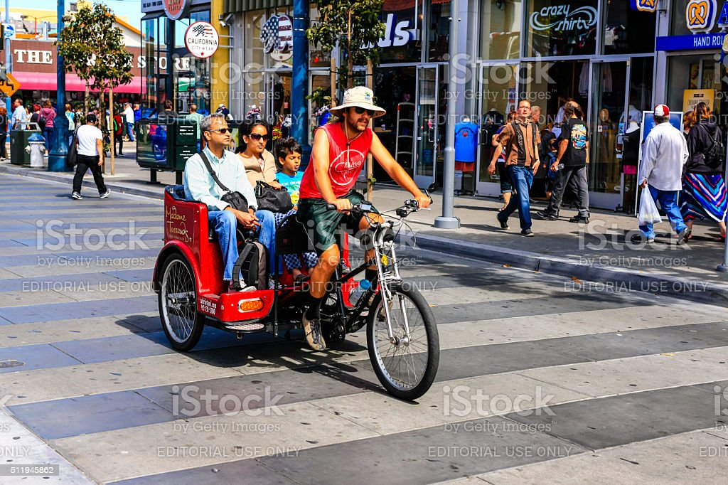 People riding in a Pediabs in San Francisco stock photo