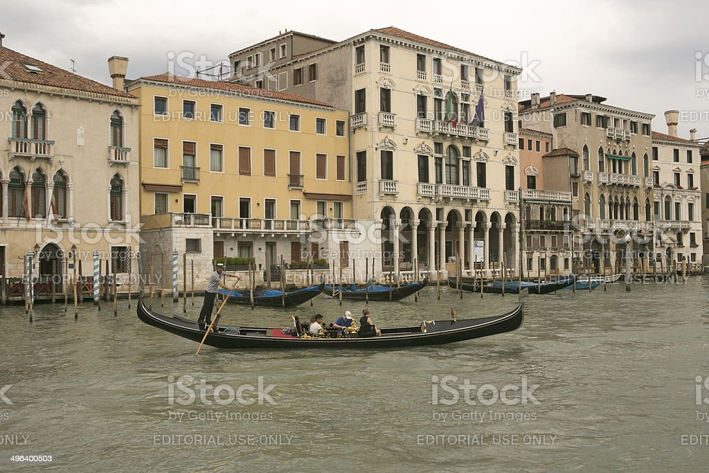 People riding traditional gondolas at water channel of venice italy stock photo