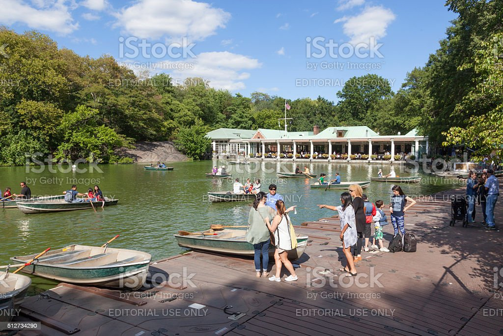 people row in boats on new york central park pond stock photo
