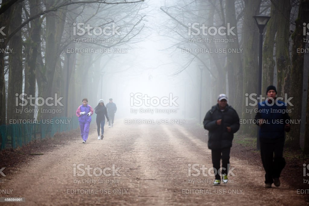 People run in a foggy country road royalty-free stock photo
