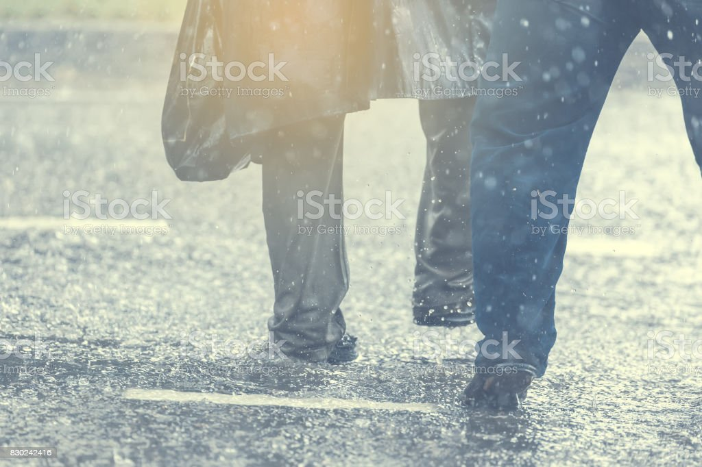 People running away through puddle at street during heavy rain. stock photo