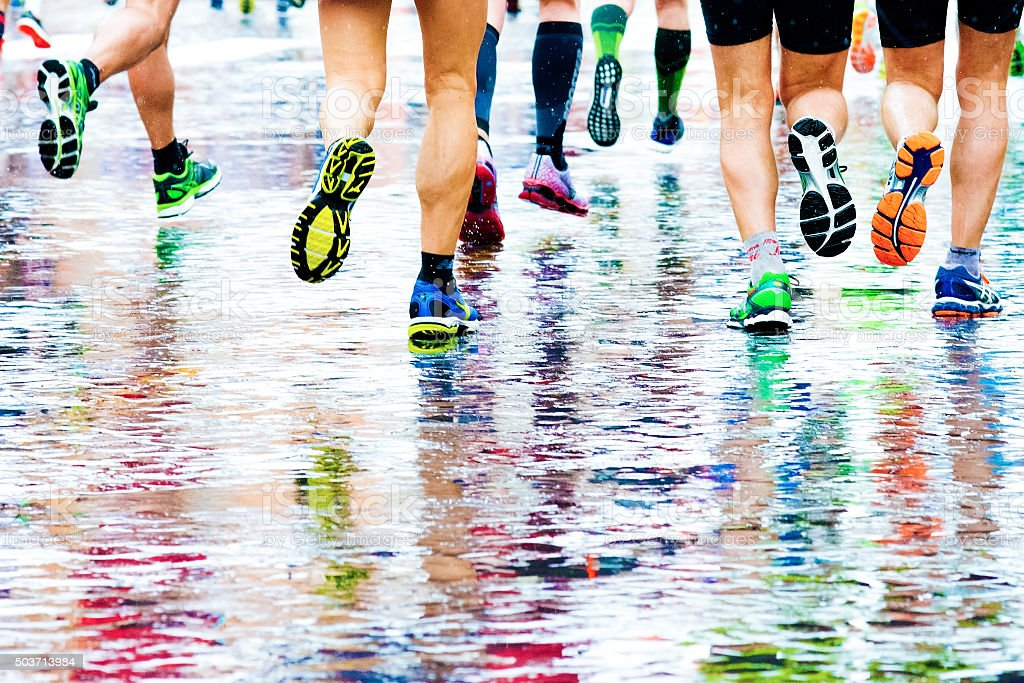 people running in a marathon on a wetted surface stock photo
