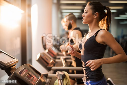 Young people exercising in a gym on treadmill. Focus is on foreground.