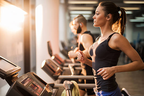 people running on a treadmill in health club. - health club stock photos and pictures