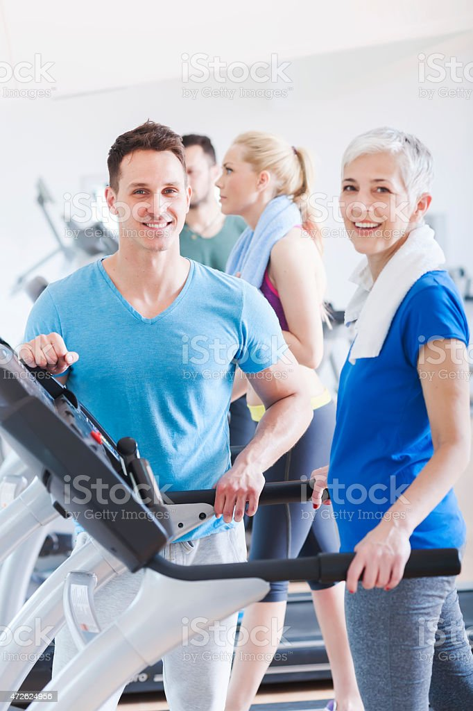 People running on treadmill at gym stock photo