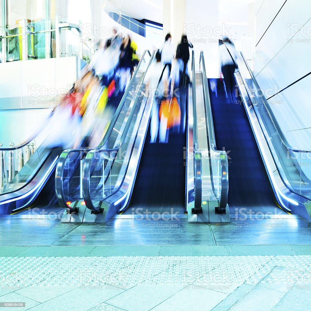 people rushing in escalators stock photo