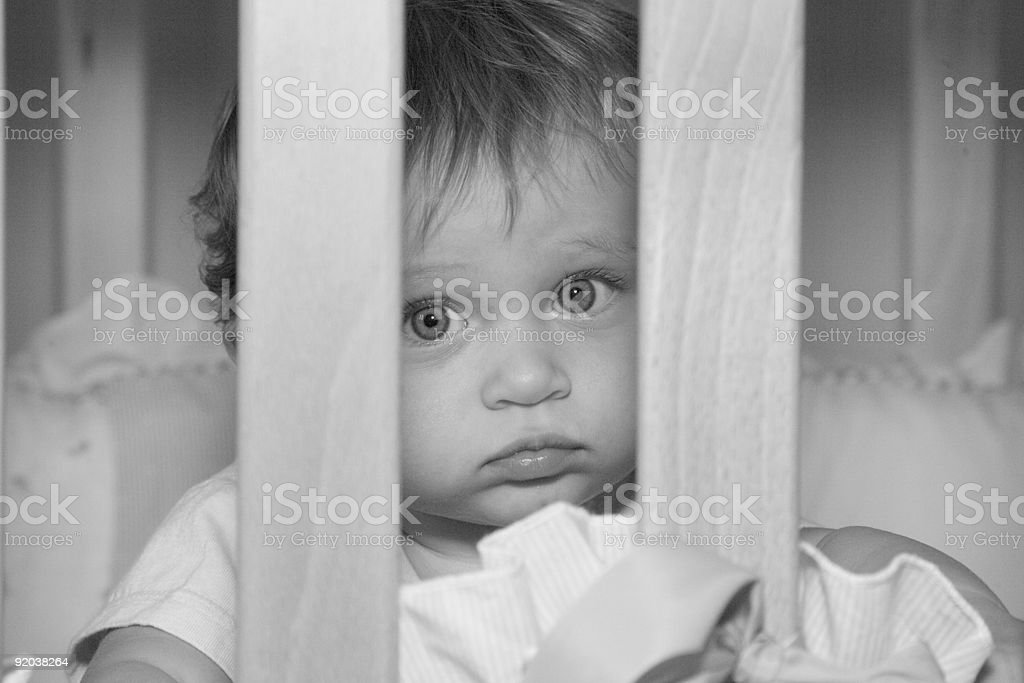 People - Sad 10 Month Old Baby Girl in Crib royalty-free stock photo