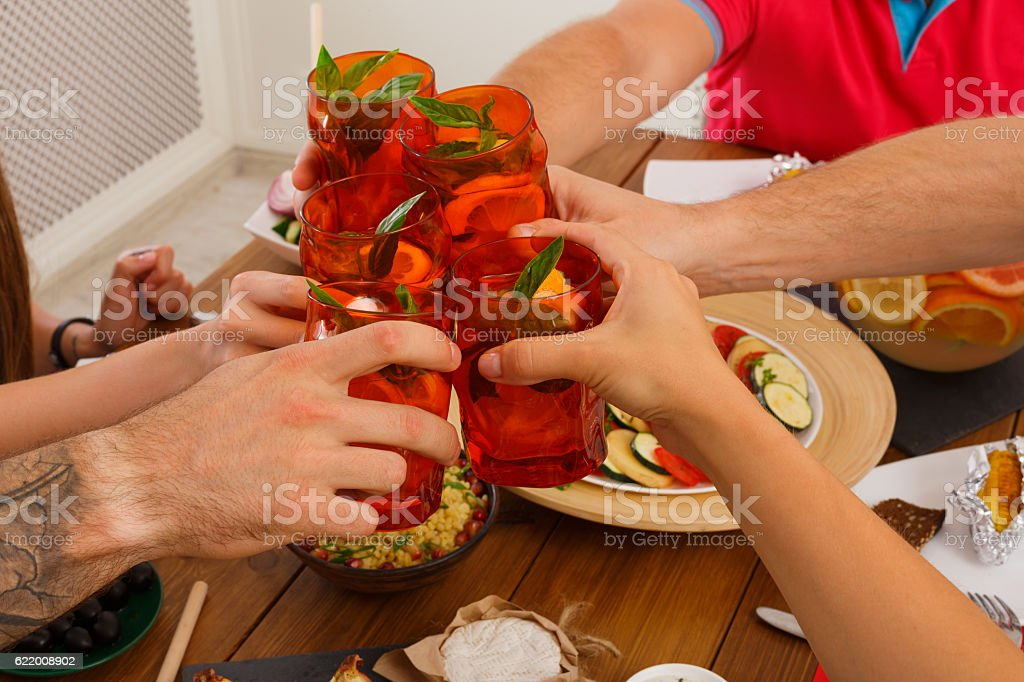 People say cheers clink cocktail glasses at festive dinner party stock photo