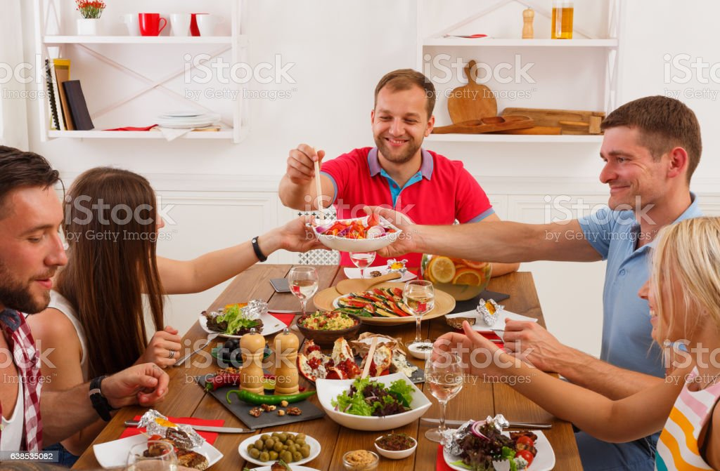 People say cheers clink glasses at festive table dinner party stock photo