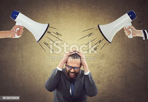 istock People screaming through megaphone at scared businessman 903659908