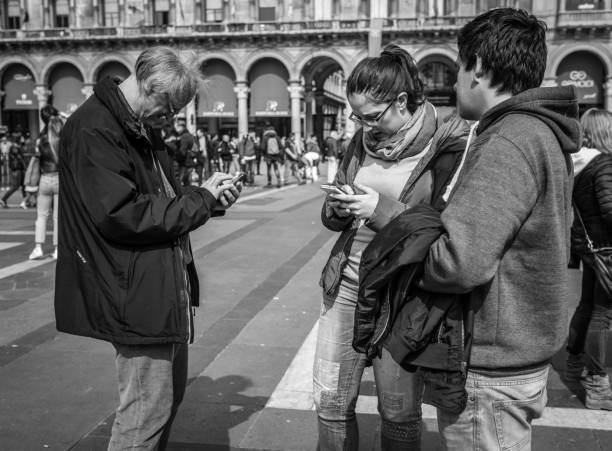 people searching something in mobile phones on the piazza del duomo square in milan, italy - giovani motorino italia parlano foto e immagini stock
