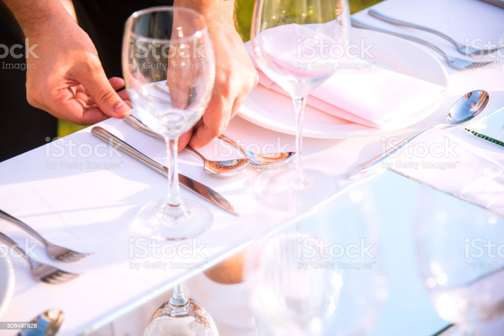 People Setting The Table For Dinner At A Wedding Stock Photo