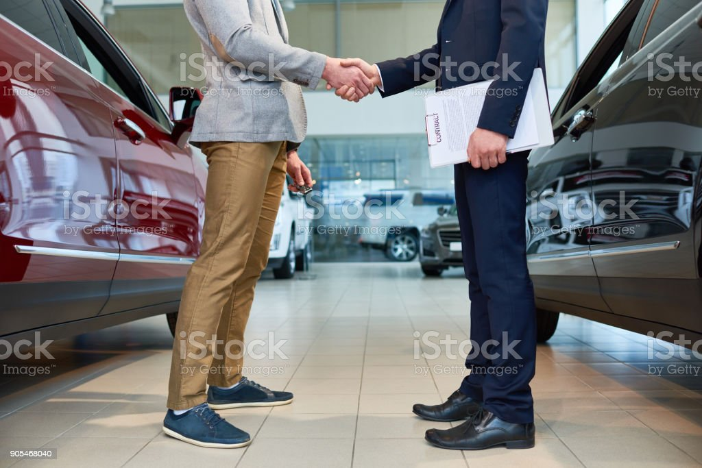 People Shaking Hands in Car Showroom stock photo