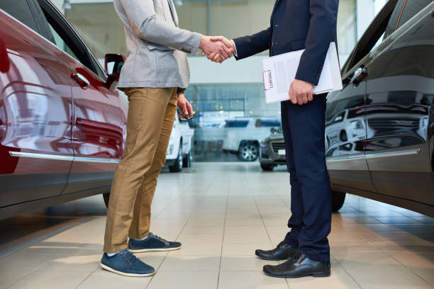 People Shaking Hands in Car Showroom Low section side view of  handsome client shaking hands with sales manager in car showroom, after buying brand new luxury car car salesperson stock pictures, royalty-free photos & images