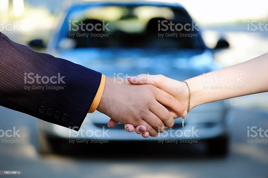 People shaking hands in front of a car after a car sale stock photo