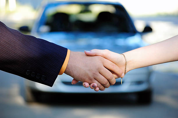 people shaking hands in front of a car after a car sale - used car selling stock pictures, royalty-free photos & images