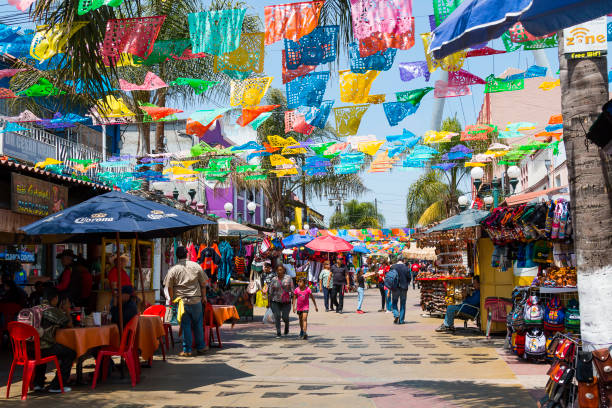 People Shop Below Colorful Hanging Flags in Tijuana, Mexico stock photo
